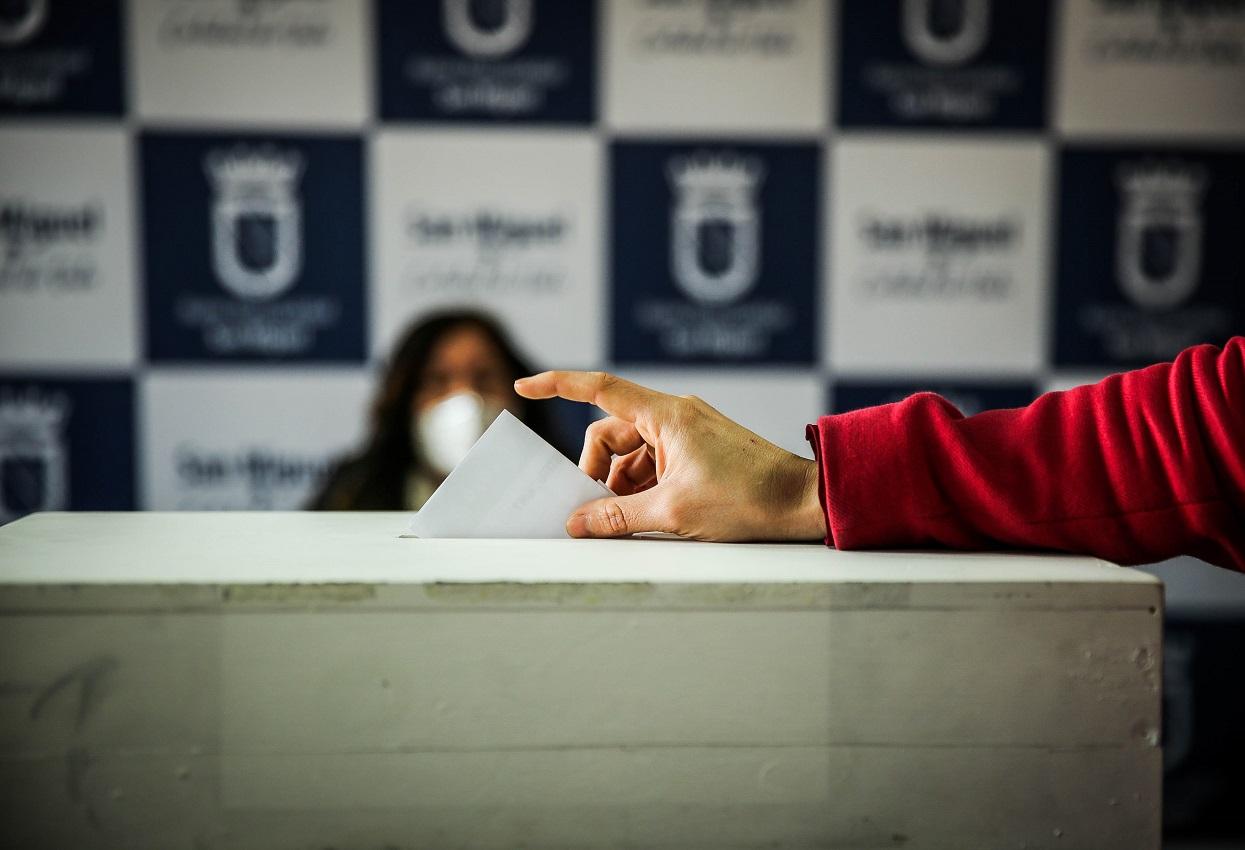 Imagen del primer plano del brazo de una persona adulto mayor votando en la urna. ?>