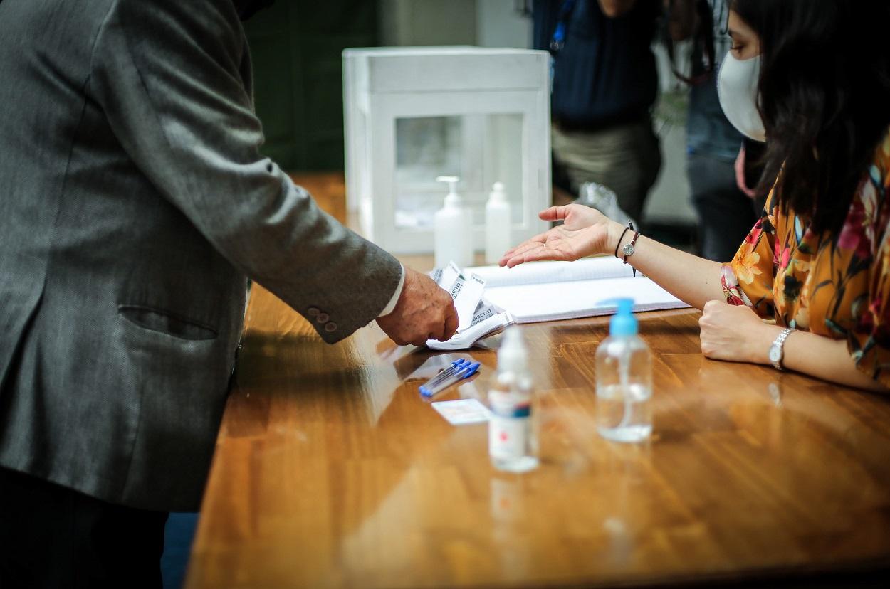 Una vocal y un votante en el proceso de votación, con urna al lado.